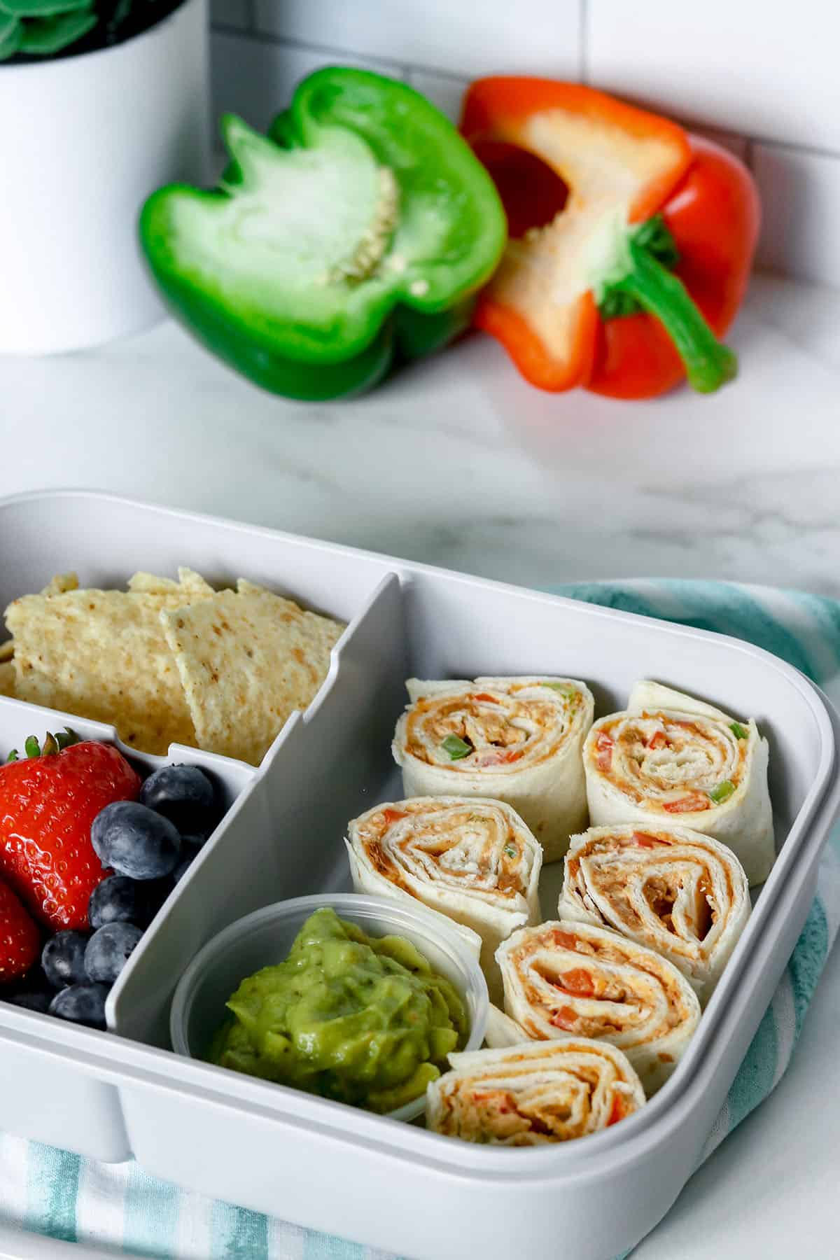 sliced taco meat pinwheels in lunch box with chips, guacamole, and fresh fruit