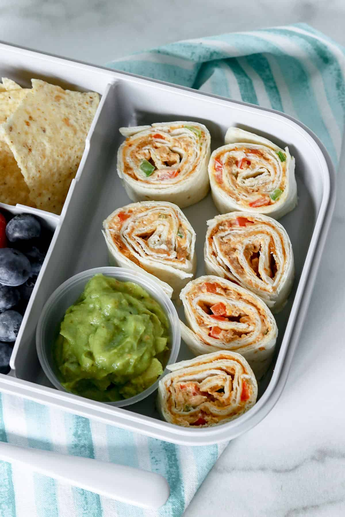 sliced taco pinwheels in lunch box with guacamole, chips, strawberries, and blueberries