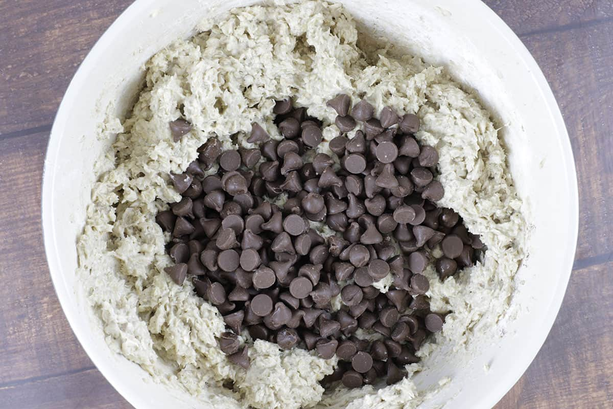 cookie dough with chocolate chips on top in a mixing bowl
