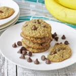 baked cookies stacked on a white plate with chocolate chips scattered around and fresh bananas in the background