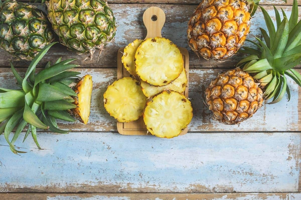 fresh pineapple cut up slices on wooden cutting board