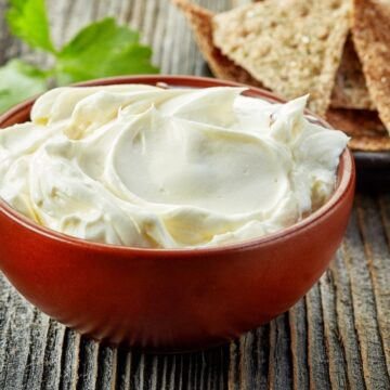 thawed and stirred cream cheese in a red bowl