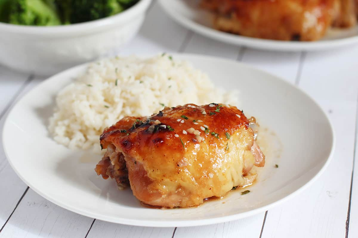 baked chicken thigh and white steamed rice on white place with broccoli in background