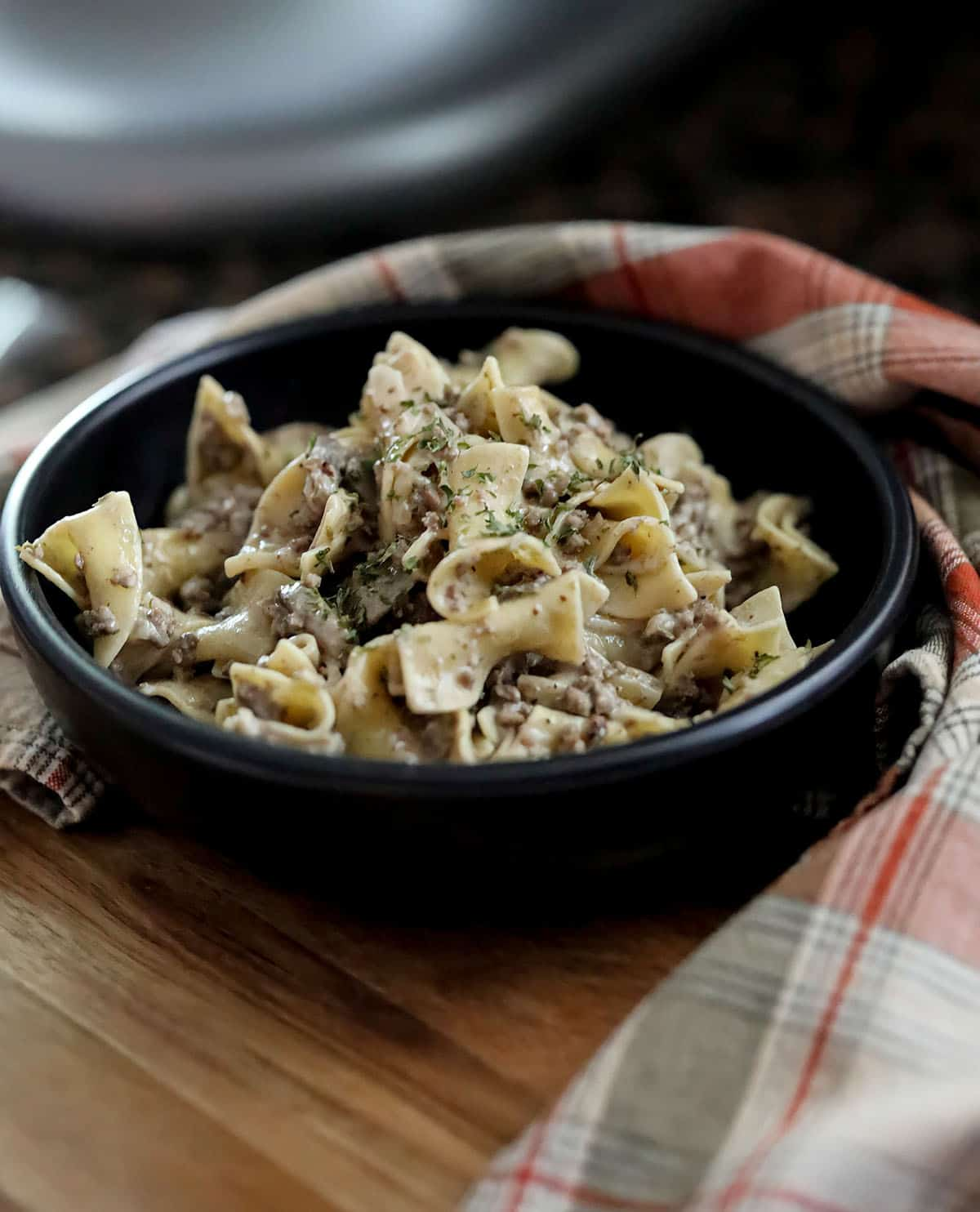 cooked stroganoff in black bowl with red plaid napkin