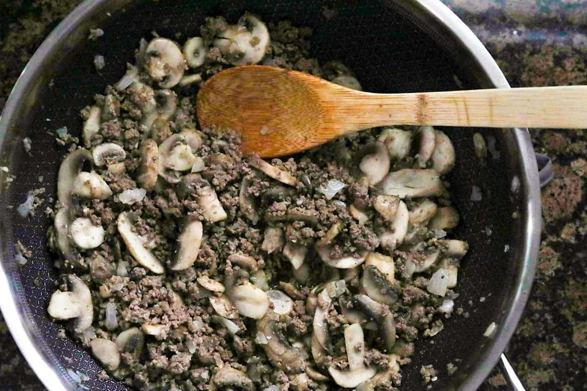 sauteed venison and mushrooms in skillet with wooden spoon